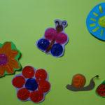 Korkendruckbild mit blumen, Schmetterling, Schnecke, Erdbeere und Sonne